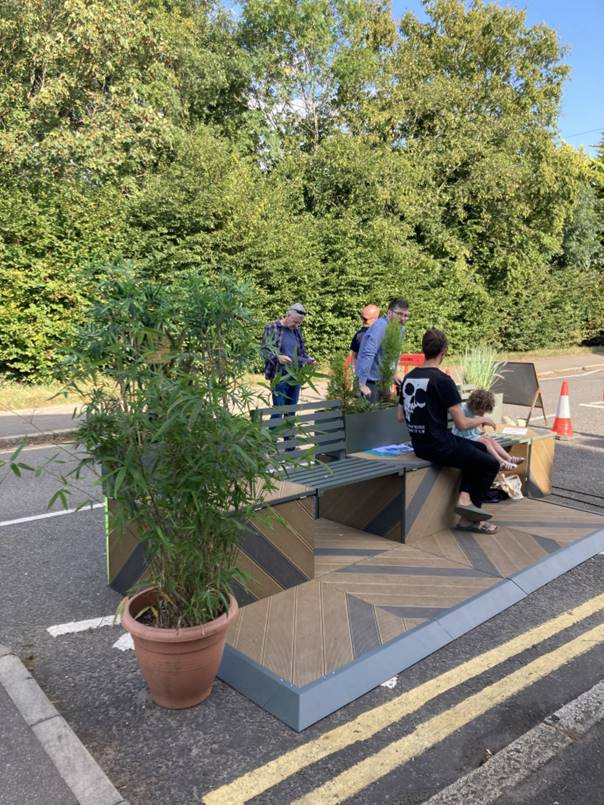 People sit on a pedlet surrounded by plants